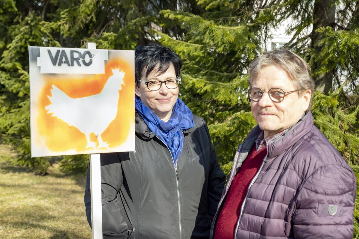 Heikki ja Leena kivimäki ja varoitus kanasta -liikennemerkki.