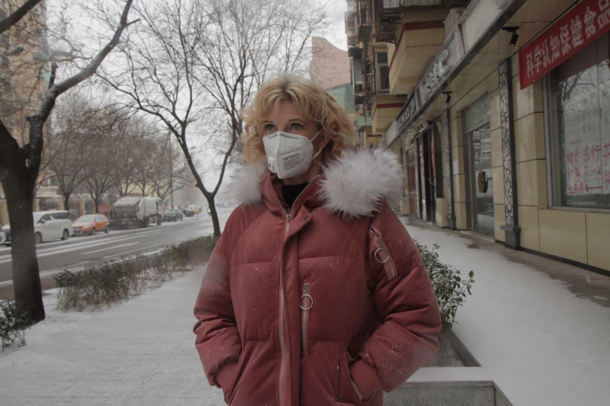 Ulla Nurmenniemi seisoo lumisella kadulla toppatakki päällä ja hengityksensuojain kasvoillaan.