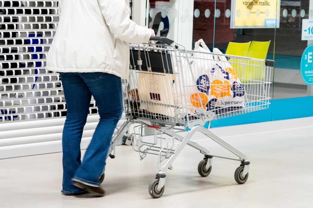 Nainen työntää ostoskärryä jossa kaupan muovikasseja ostoksineen.