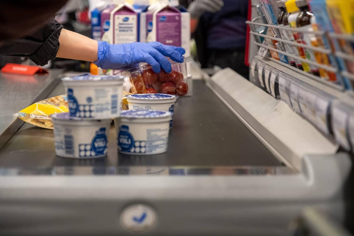 Suojakäsineellä suojattu käsi nostaa ostoksia elintarvikemyymälän liukuhihnalle.
