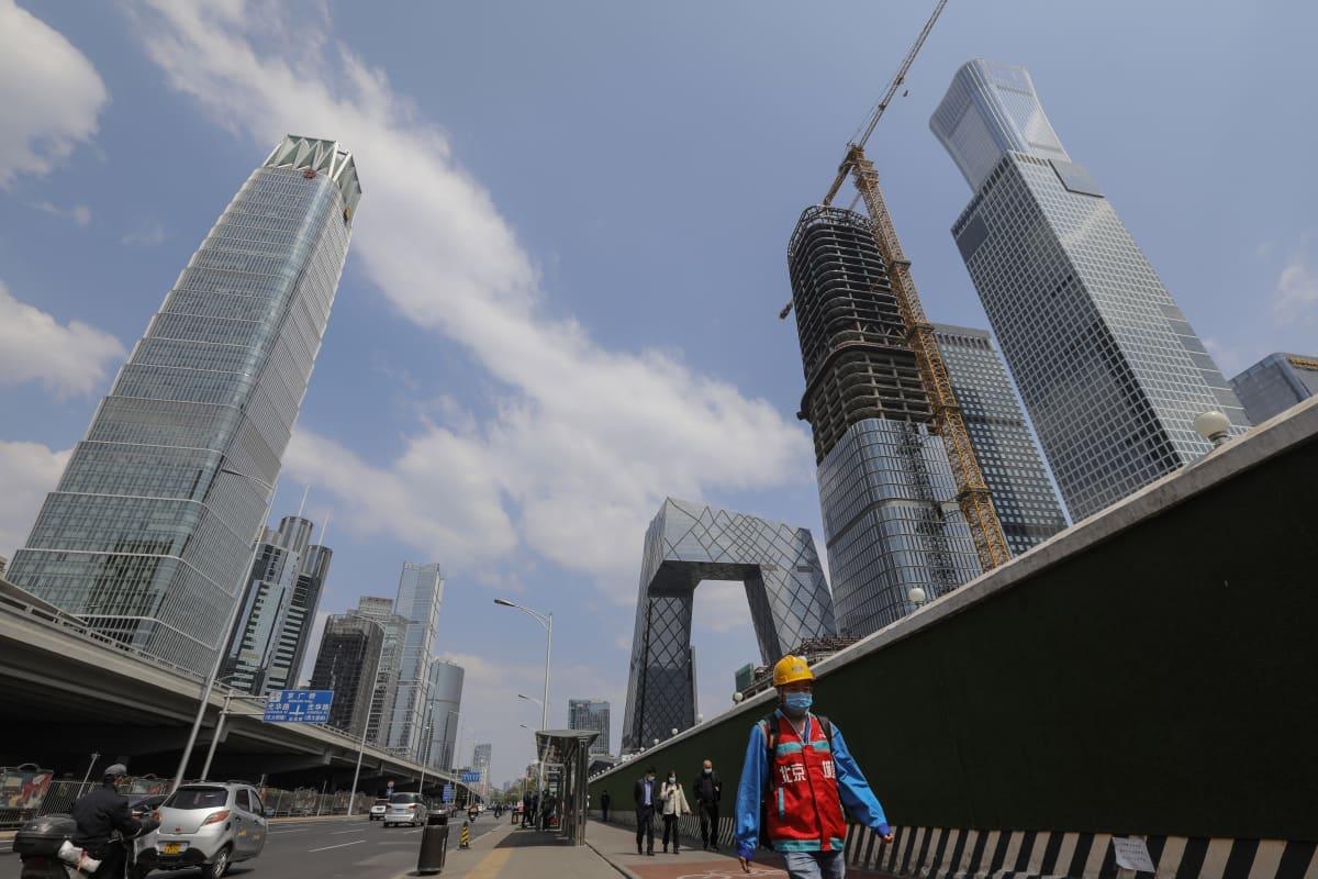 rakennusmies kävelee Pekingissä korkeiden kerrostalojen lomitse