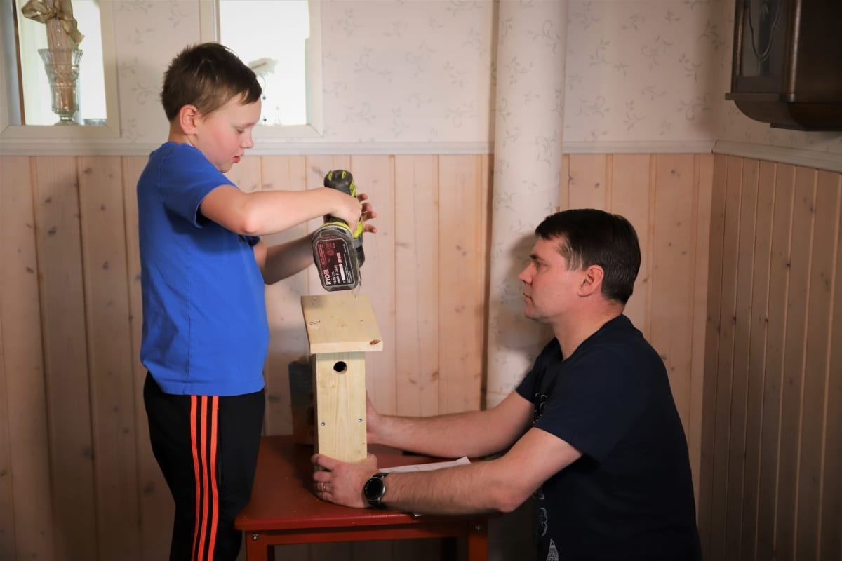 Akseli poraa linnnunpönttöä isän avustuksella etäkolussa