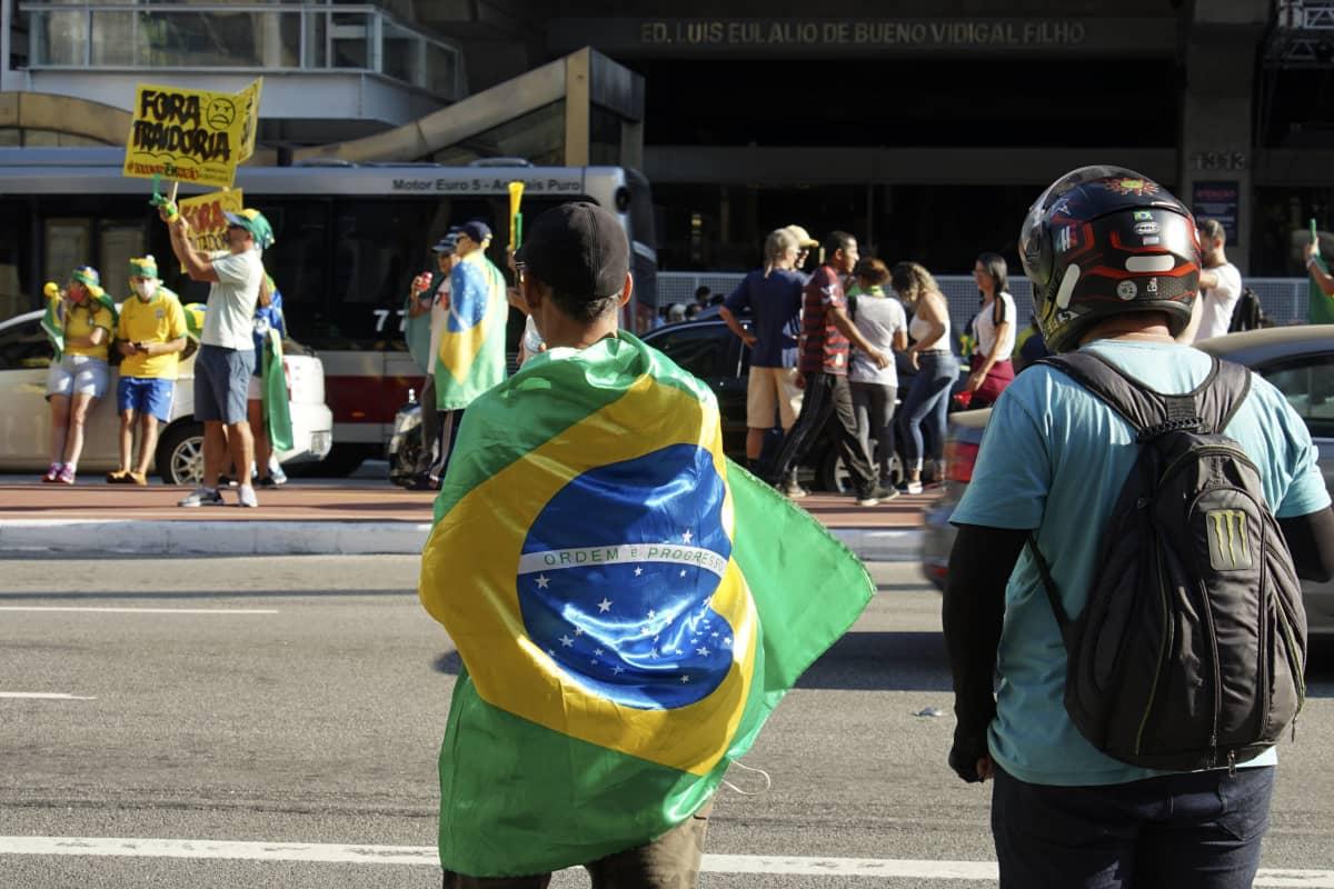 Mielenosoittajia kadulla, lähinnä kameraa oleva henkilö kietoutunut Brasilian lippuun