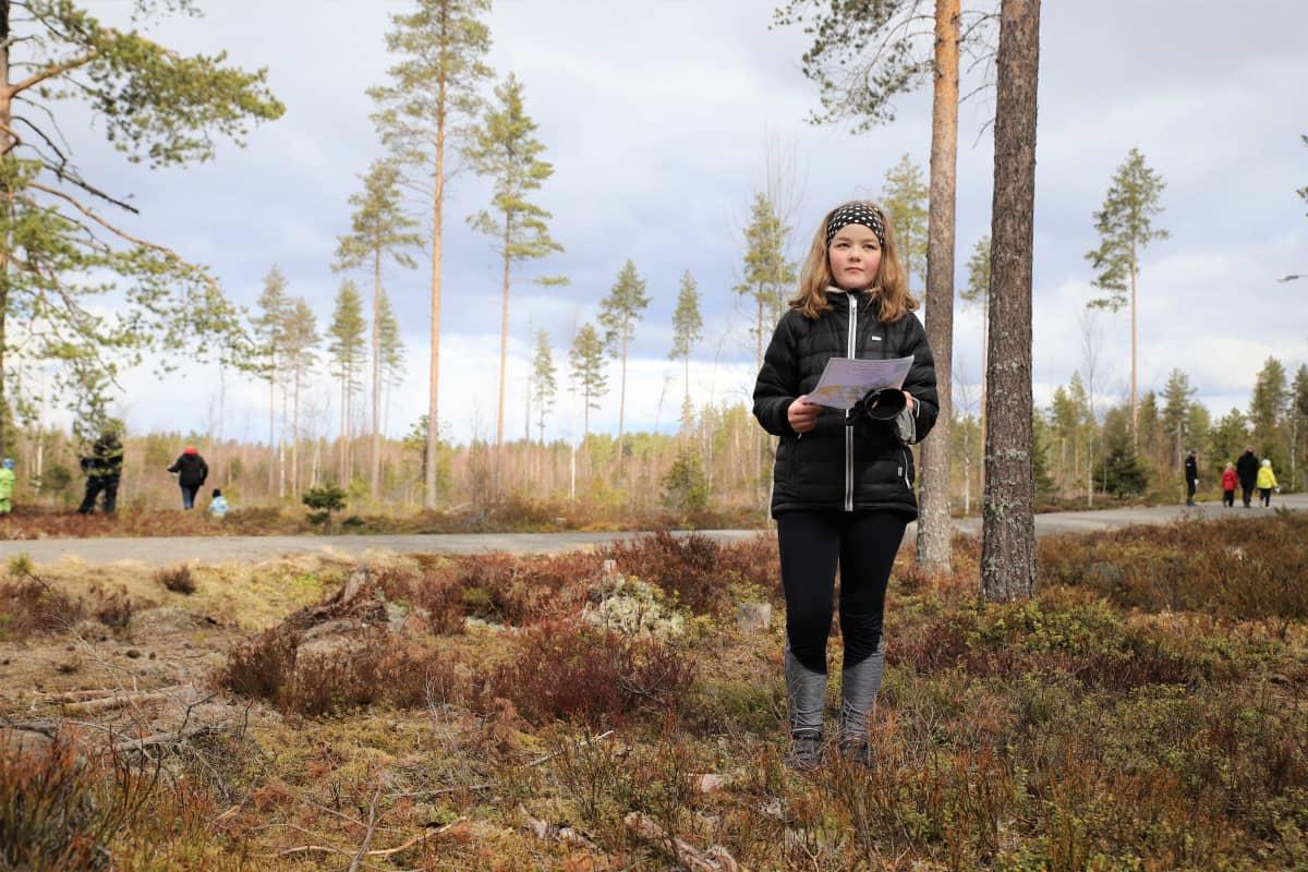Anni Penninkangas seisoo kartan kanssa metsässä Alajärven kuntoradan maastossa
