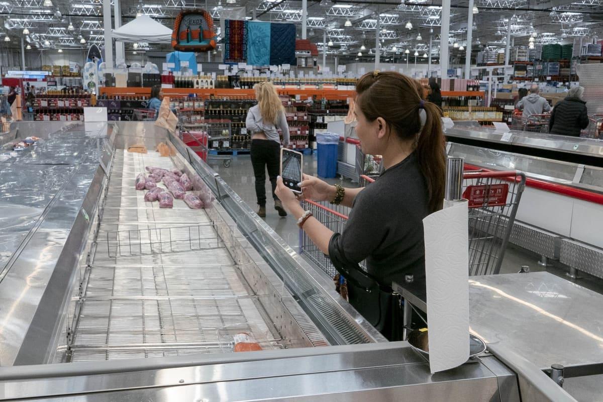 Nainen kuvaa lähes tyhjää liha-allasta kaupassa.