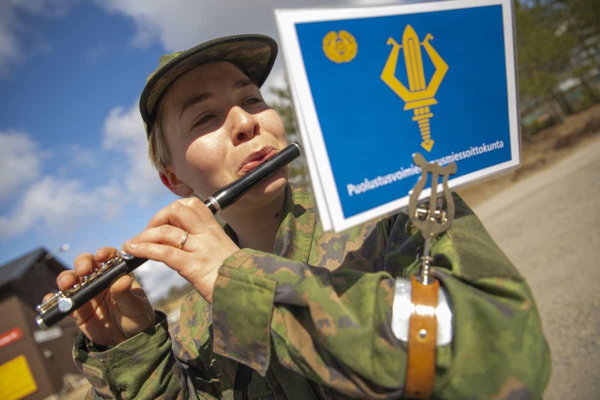 Puolustusvoimien varusmiessoittokuntaan kuuluva Sonja Kohtala soittaa puhallinsoitinta ulkona auringonpaisteessa.