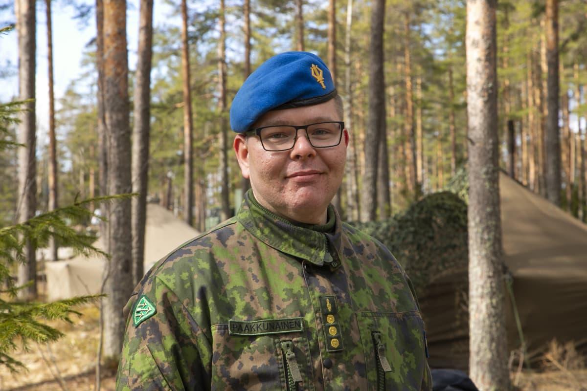 Varusmiessoittokunnan musiikkikapteeni Ville Paakkunainen katsoo kohti kameraa metsässä.