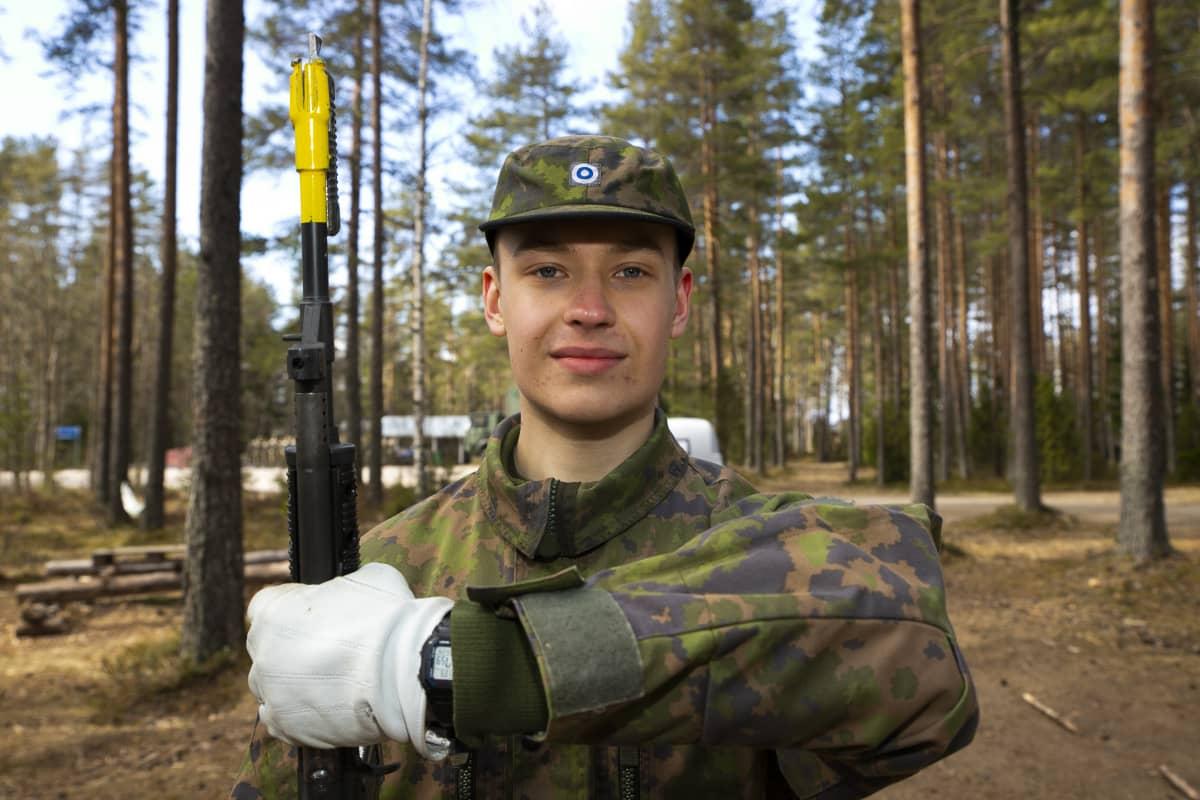 Varusmiessoittokuntaan kuuluva Lauri Heroja pitelee kivääriään ja katsoo kameraan metsässä.
