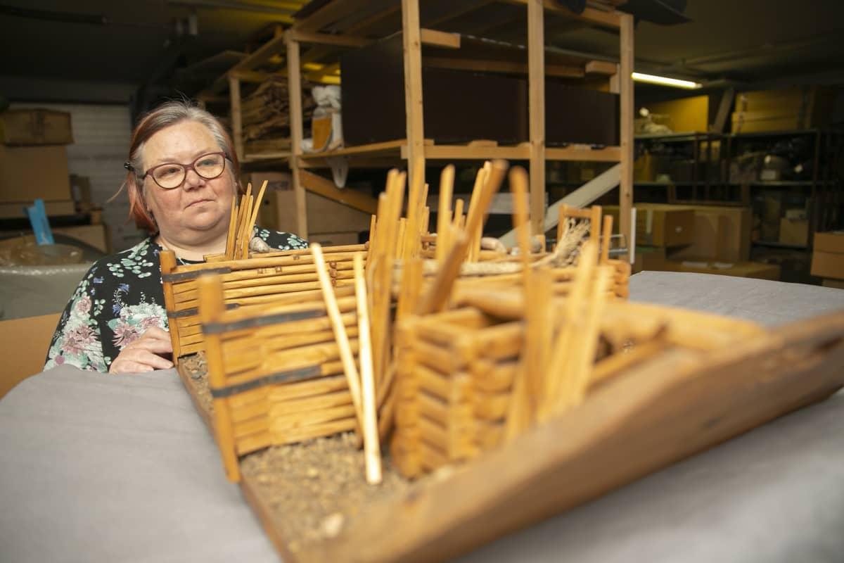 Silmälasipäinen nainen tarkastelee vanhaa ankeriaspadon pienosmallia