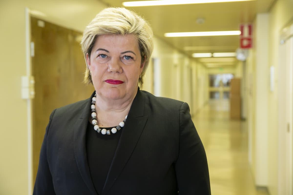 Johtajaylihoitaja Kirsi Leino Kanta-Hämeen keskussairaalasta seisoo hallintorakennuksen käytävällä.