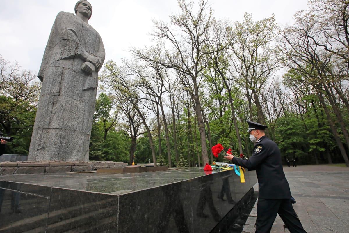Sotilas asettaa kukkia patsaan juurelle. Patsas esittää vakavaa naishahmoa. Sotilaalla on kasvoillaan kasvomaski.