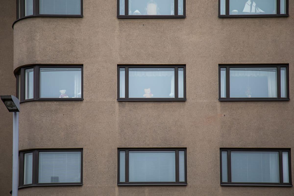 Nalleja kerrostalon ikkunoissa.