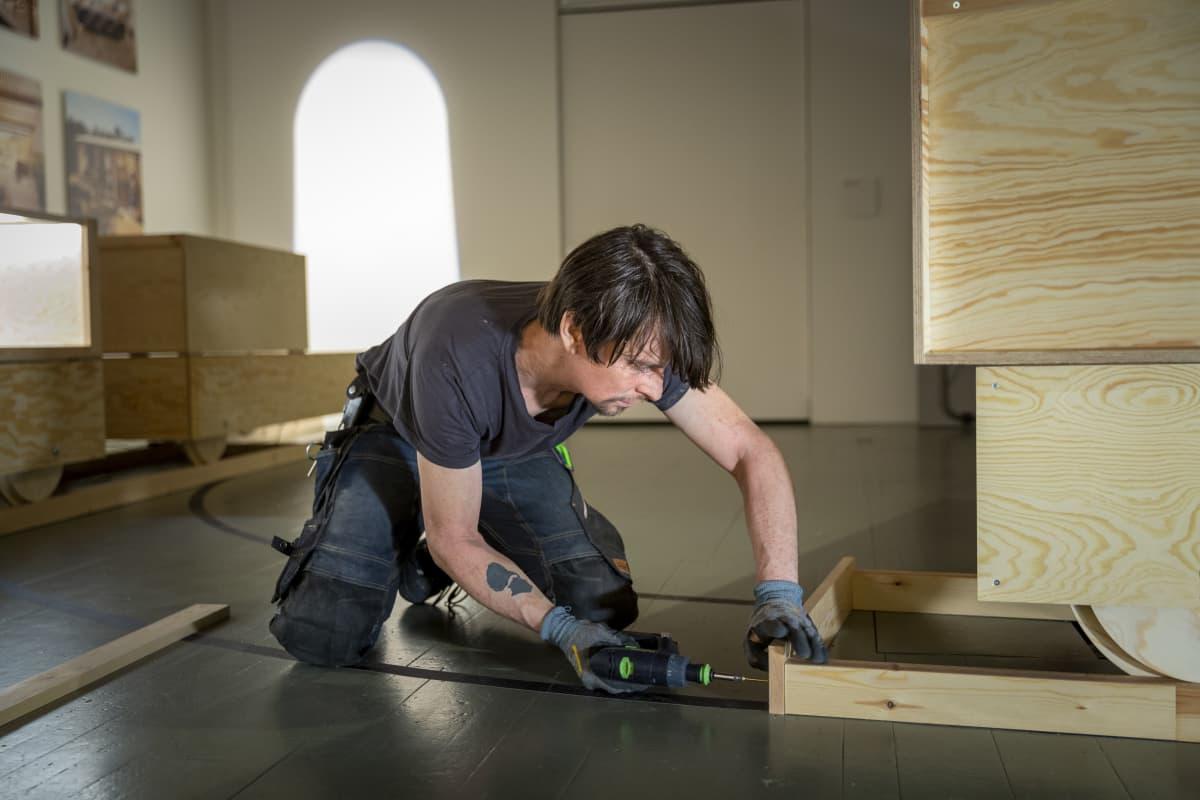 Näyttelymestari Ville Särmä kokoaa näyttelyrakenteita.