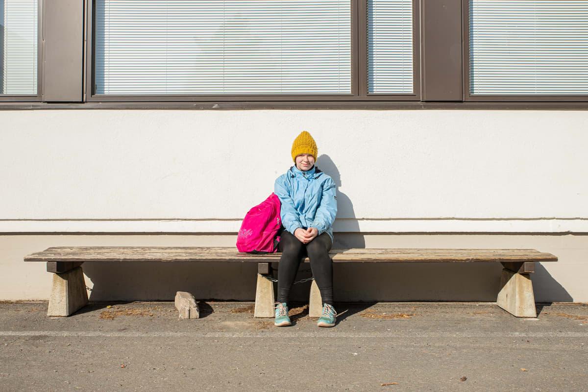 Sonja Manninen istuu koulun pihalla.
