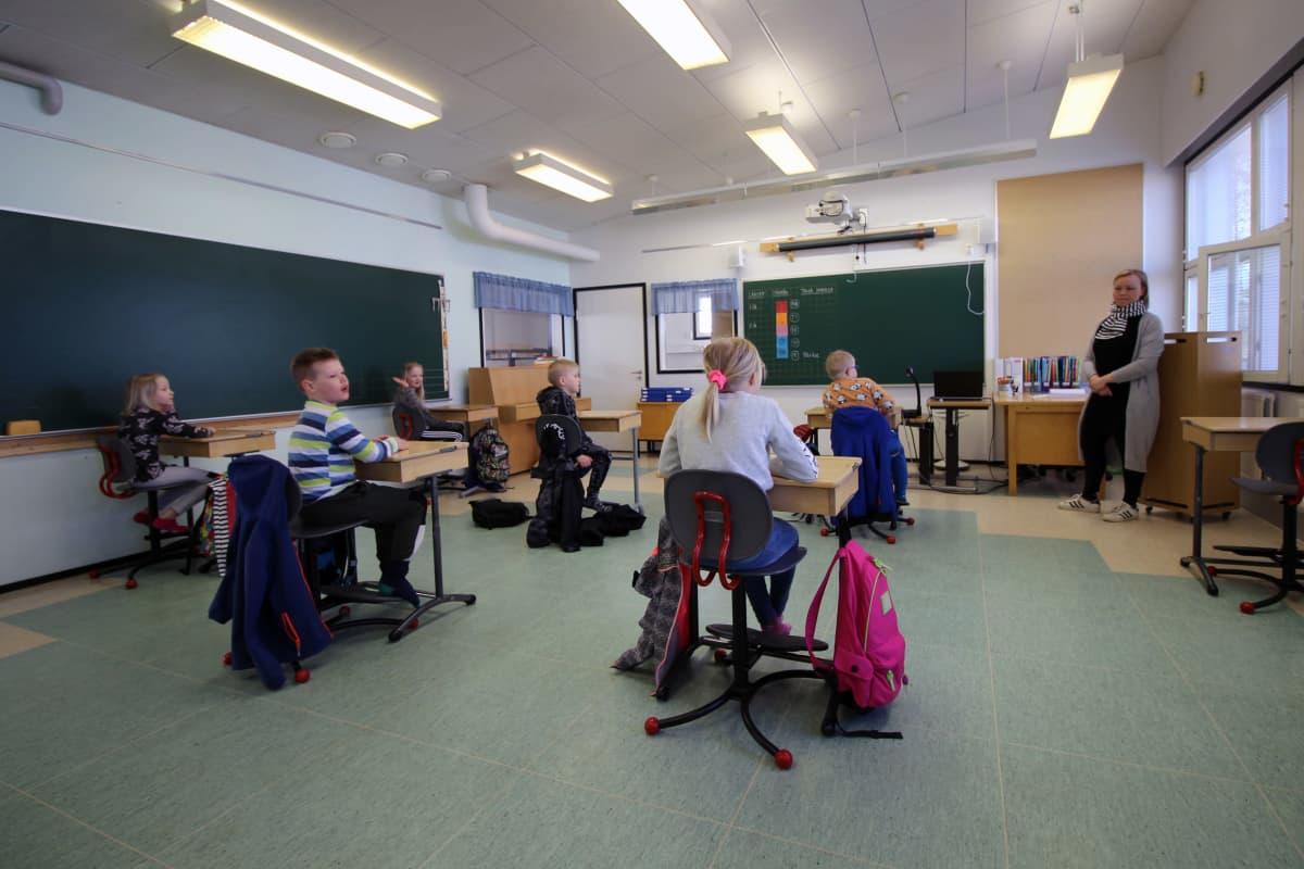 Pieni ryhmä kakkosluokkalaisia istuu pulpeteissaan, jotka on järjestetty turvavälietäisyyksille. Luokan edessä opettaja.