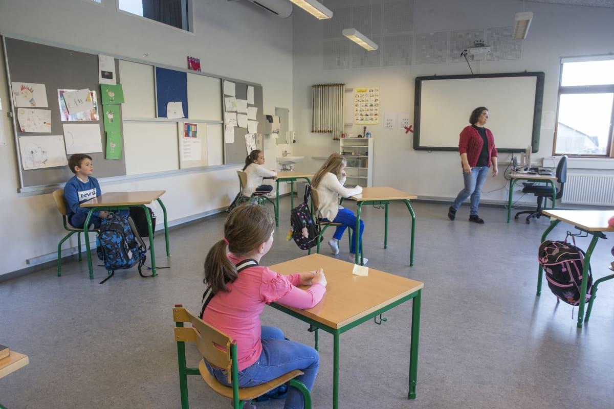 Koululaiset istuvat turvaetäisyyden päässä toisistaan luokassa.