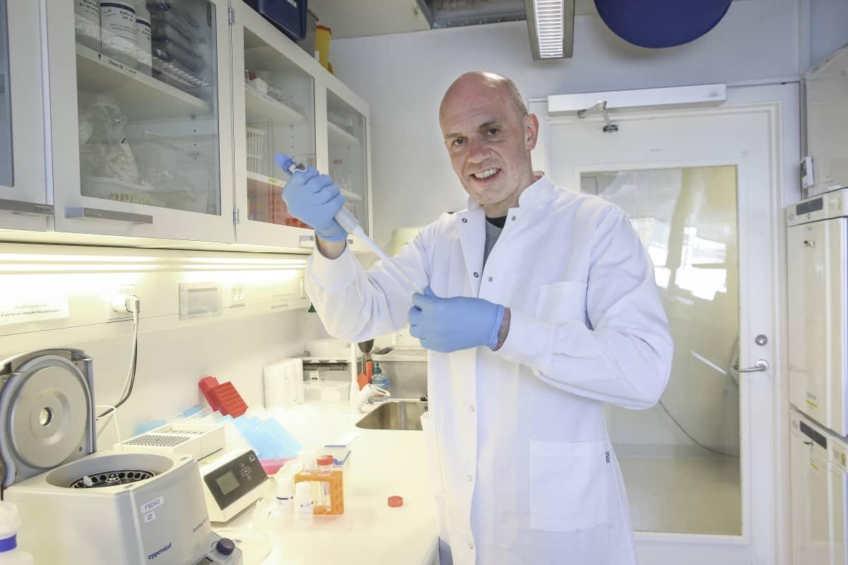 Valkotakkinen mies tekemässä virustestiä laboratoriossa.