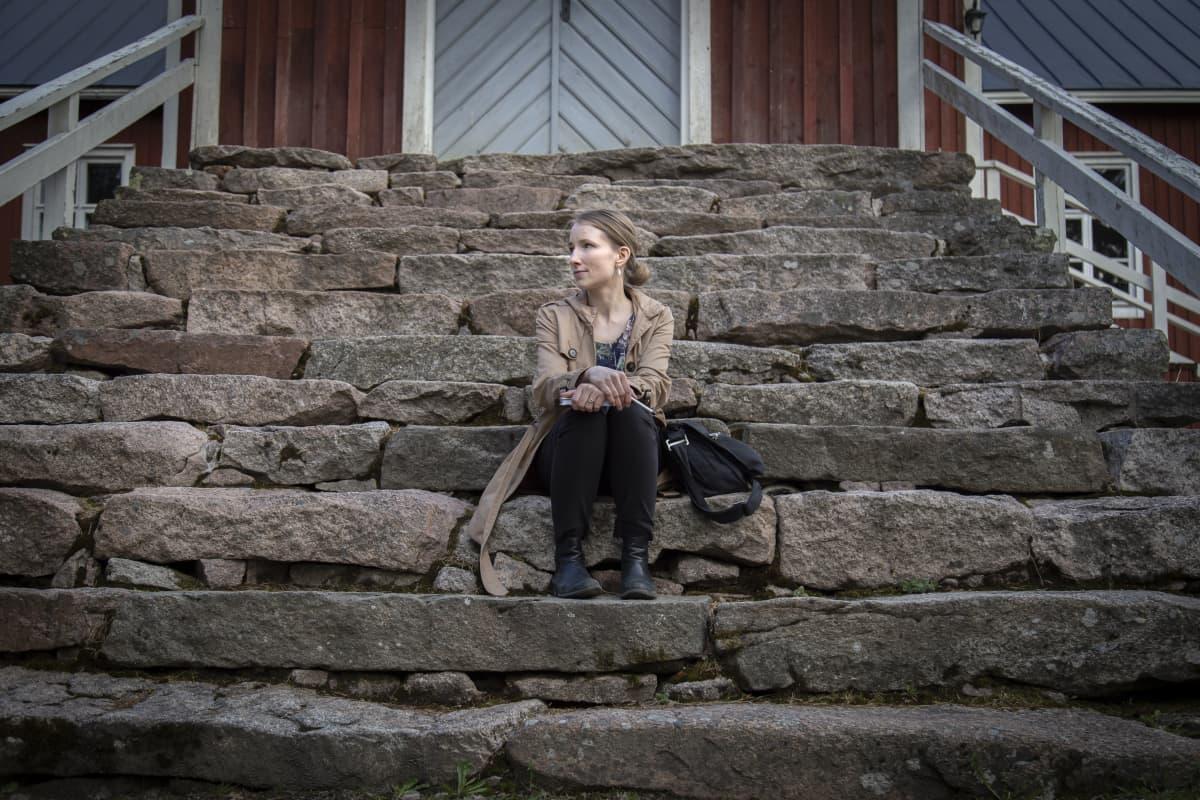 Sanoittaja Tuuli Charalambous poseraa kameralle Haapajärven kirkon portailla.