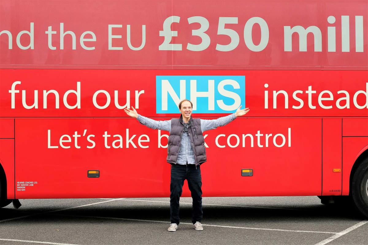 Dominic Cummingsia esittävä Benedict Cumberbatch seisoo kädet levällään punaisen kaksikerroksisen bussin edessä. Bussin kyljessä on brexit-kampanjan iskulauseita.