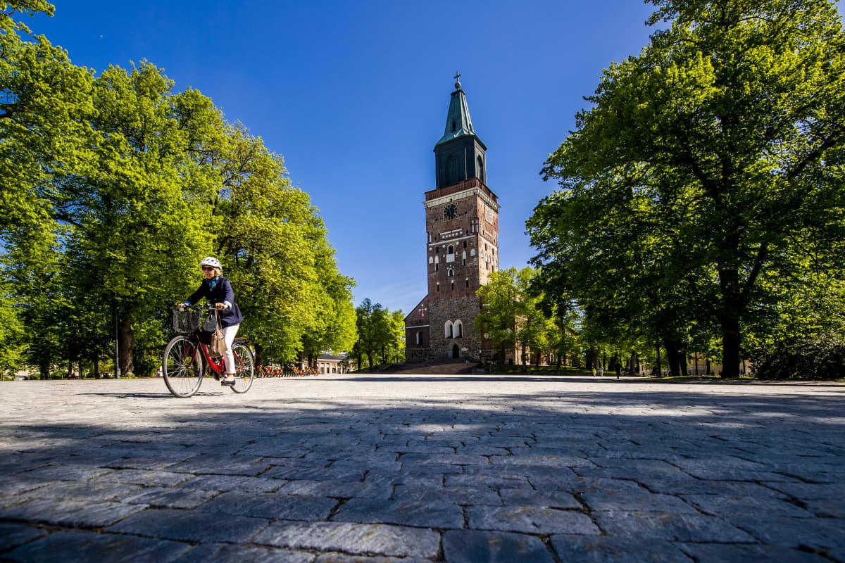 En kvinna cyklar över domkyrkoskvären i Åbo.