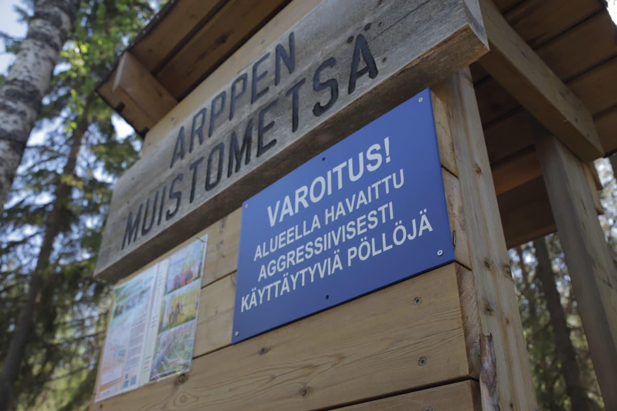 """Arppen muistometsäkyltti, jonka alla lukee """"varoitus! alueella havaittu aggressiivisesti käyttäytyviä pöllöjä""""."""