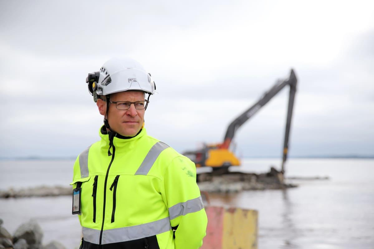 Janne Ikonen Savon Kuljetukselta seuraa lossirannan rakennustöiden etenemistä Liperissä, taustalla kaivinkone.
