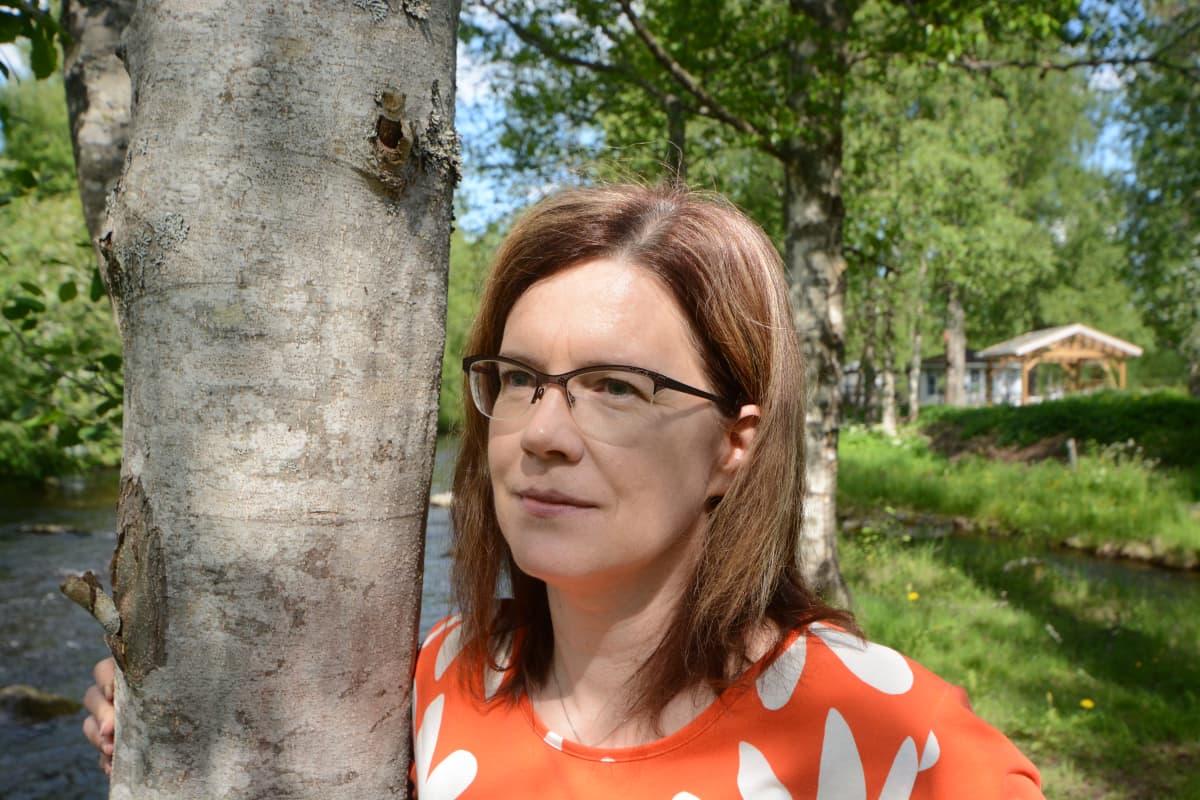 Sari Hyttinen nojaa puuhun ja katselee joelle.