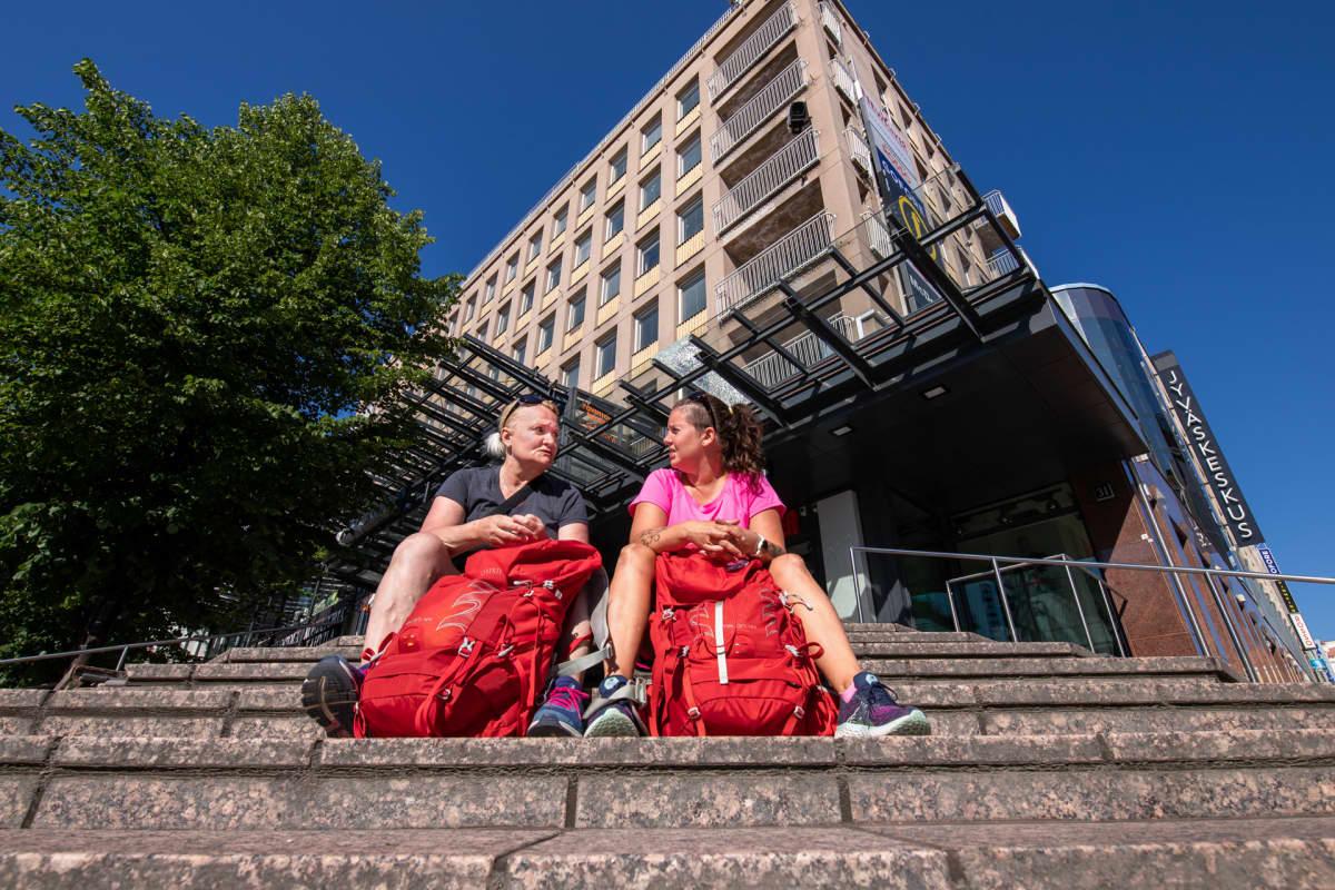 Tukialus-hankkeen Minna Lapisto ja Katja Hartikainen istuvat portailla Jyväskylän keskustassa.