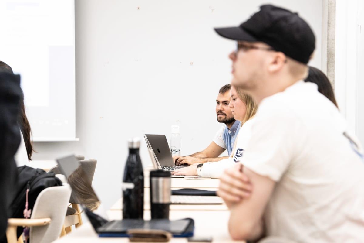 Aalto-yliopiston kesäkurssin opiskelijoita luokkahuoneessa ja etäyhteydellä mukana muita opiskelijoita ympäriä Suomean ja muuta maailmaa.