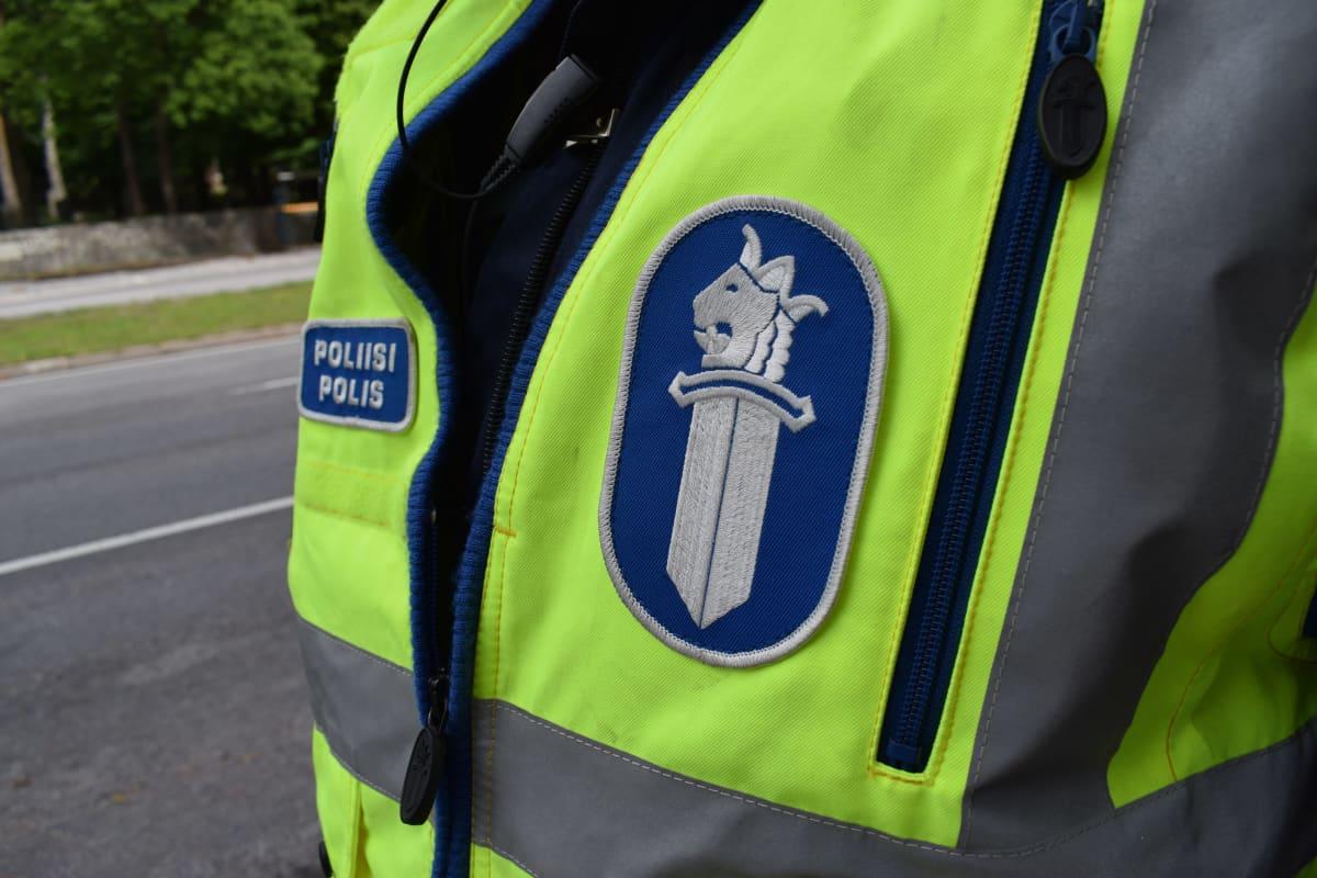 Poliisin turvaliivi, jossa poliisin logo.