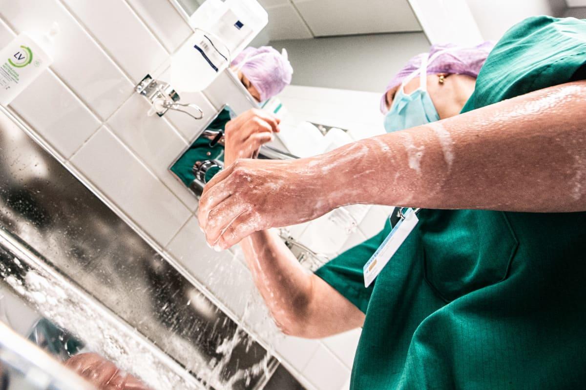 Leikkaussalihoitaja Carita pesee käsiään ennen leikkaussaliin menoa.