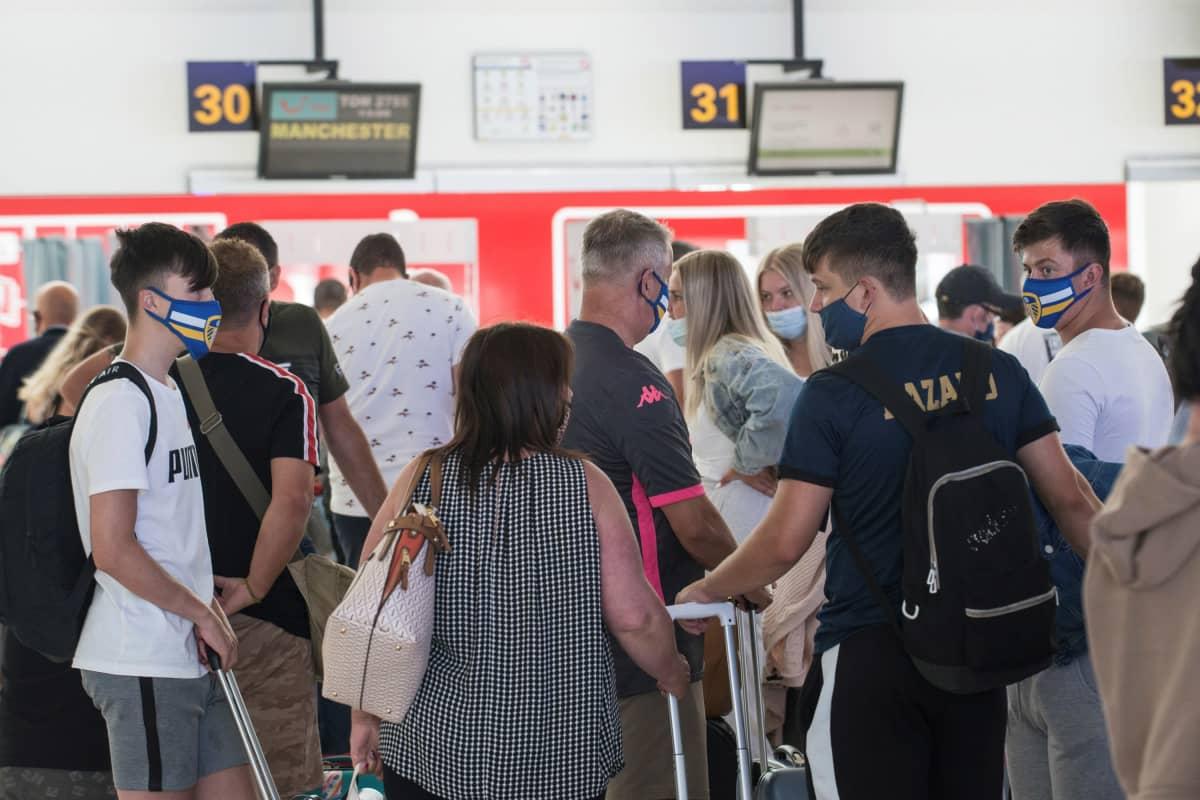 Turisteja matkalaukkuineen jonossa lähtötiskin edessä.