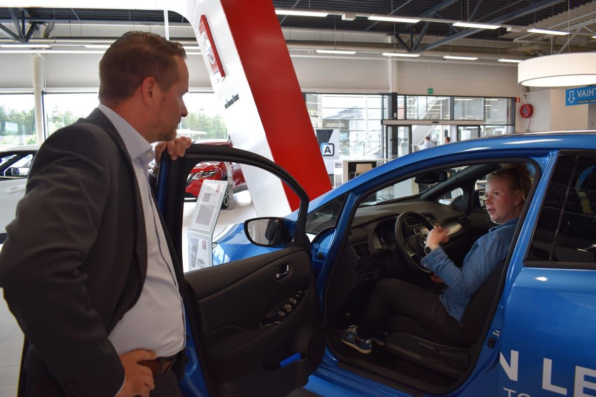Myyntipäällikkö Sami Tuomialho esittelee Nissanin sähköautoa Anni Peltomaalle..