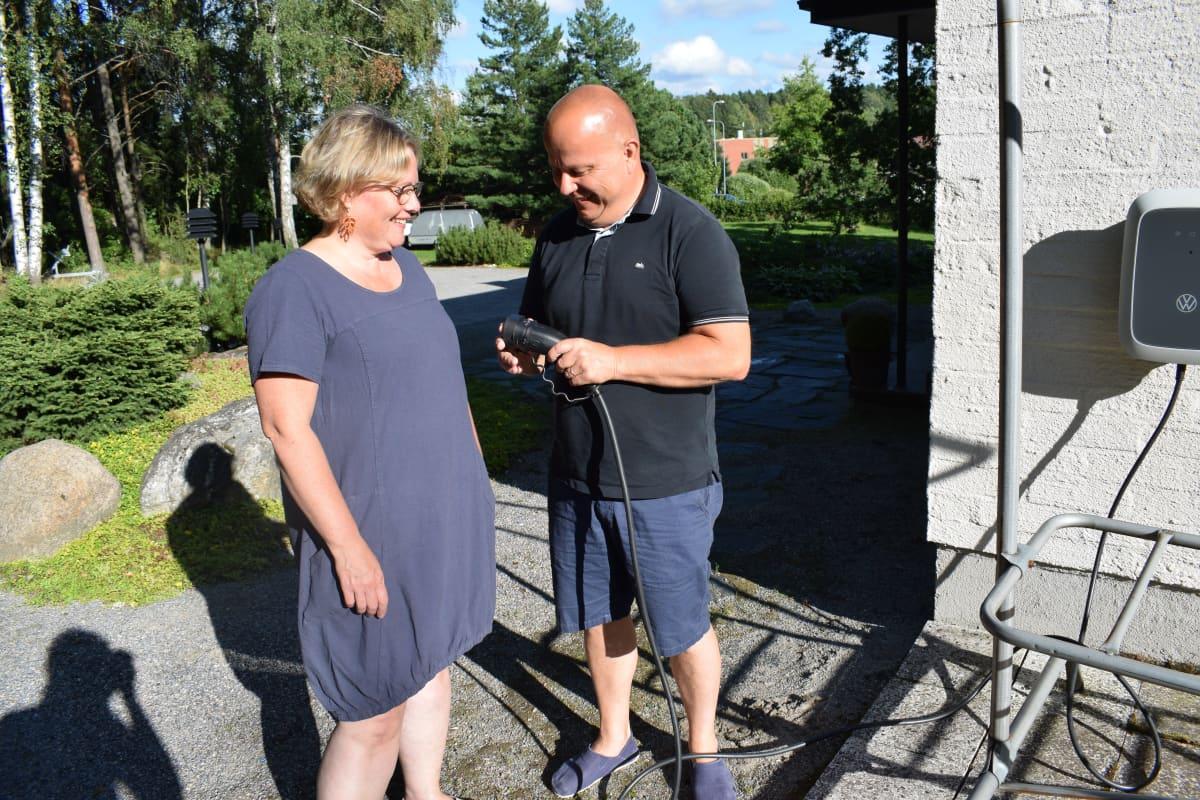Kirsi ja Jari Nuutinen tutkivat sähköauton latauspistoketta.