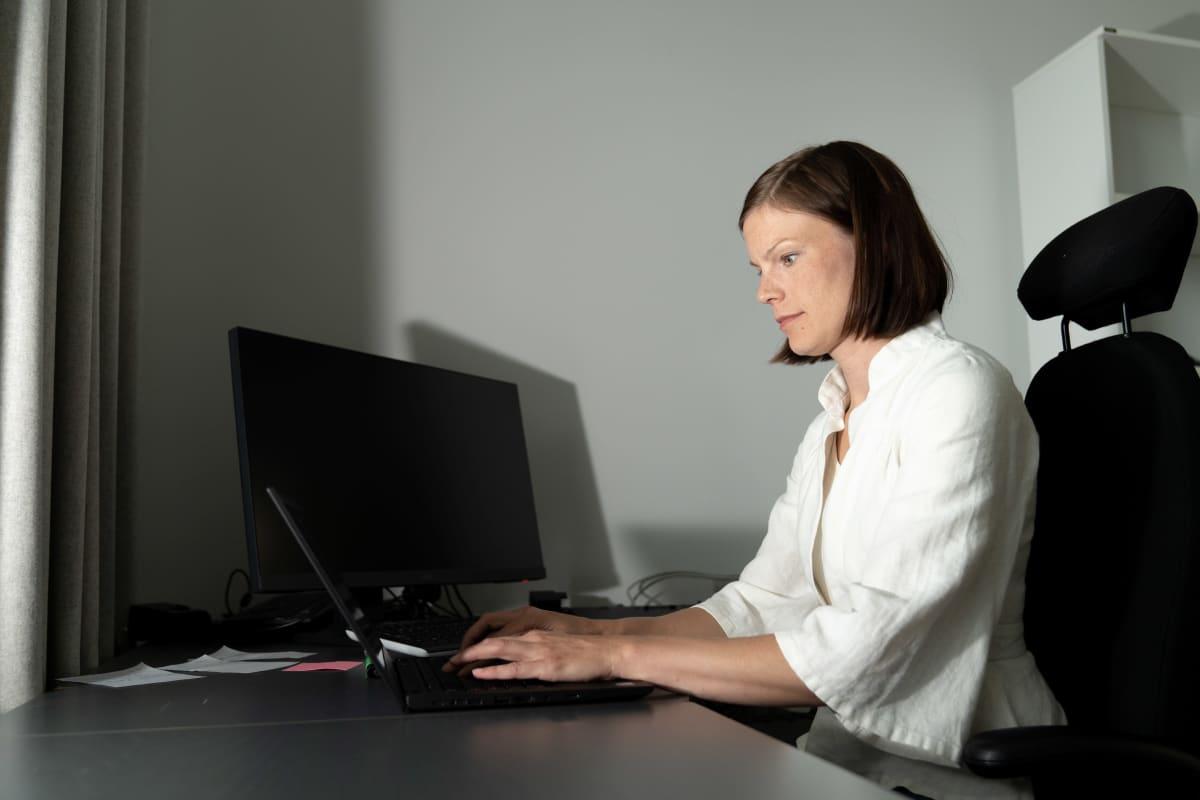 Sanna Kurronen istuu pöydän ääressä toimistossaan.