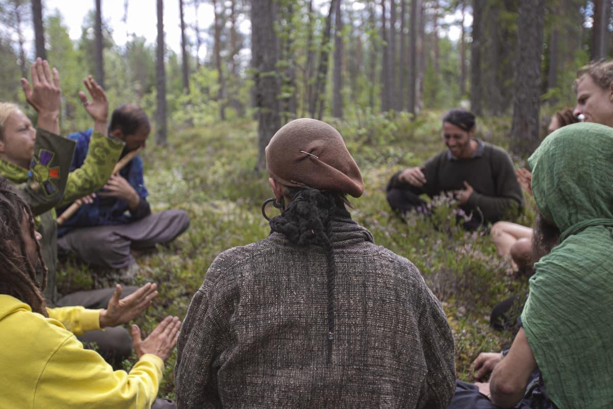 Hippiyhteisö Rainbow on kokoontunut ringissä soittamaan metsään