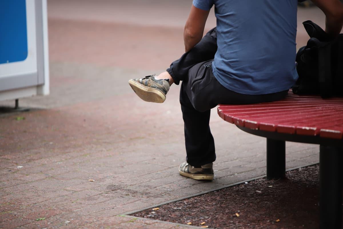 Mies istumassa Porin kävelykadulla.