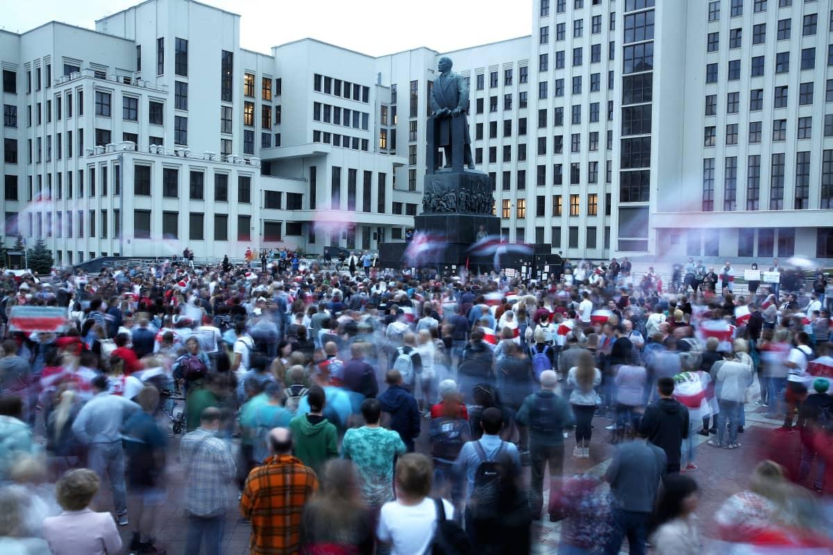 Suuri joukko ihmisiä seisoo aukiolla. Kuva-alan keskellä näkyy patsas. Aukion laidalla on laatikkomaisia vaaleita kerrostaloja.