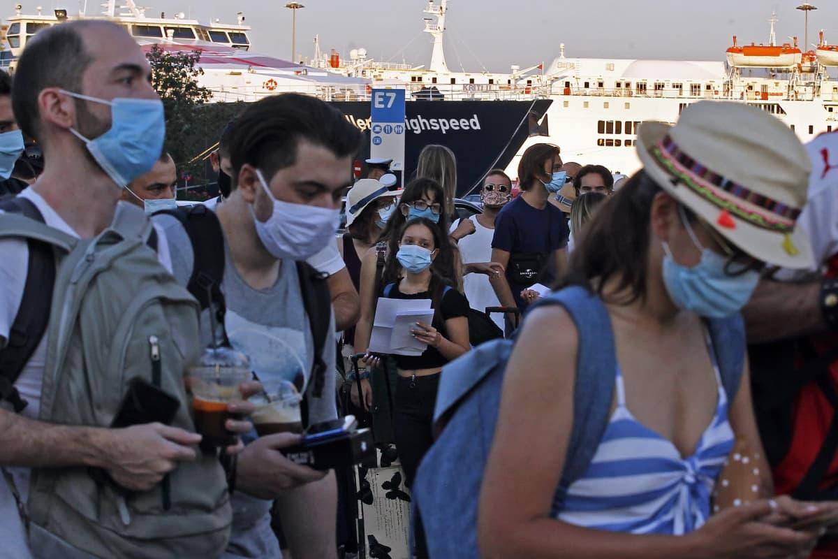 Turisteja maskit päällä.