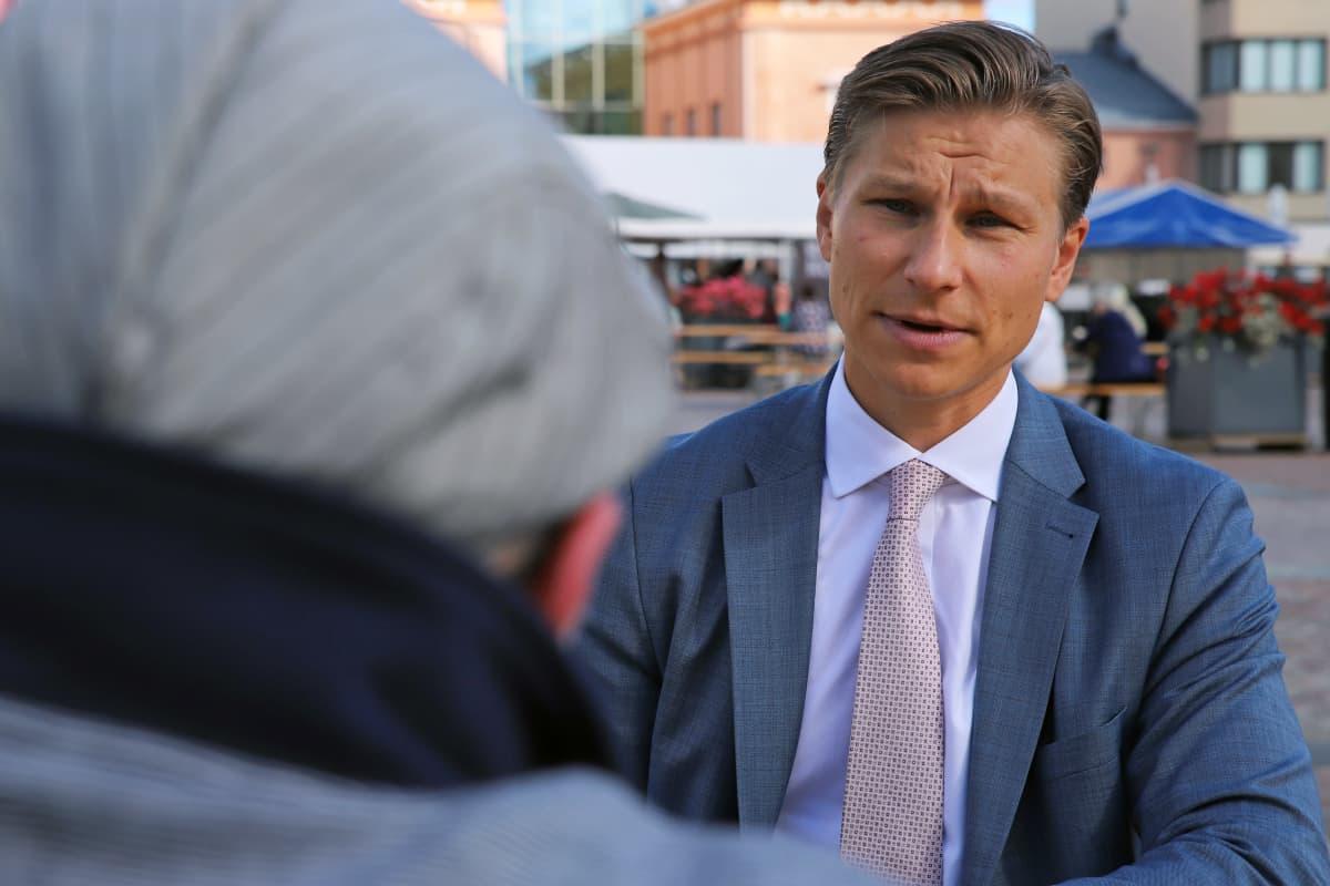 Antti Häkkänen keskustelee toimittajan kanssa Mikkelin torilla.