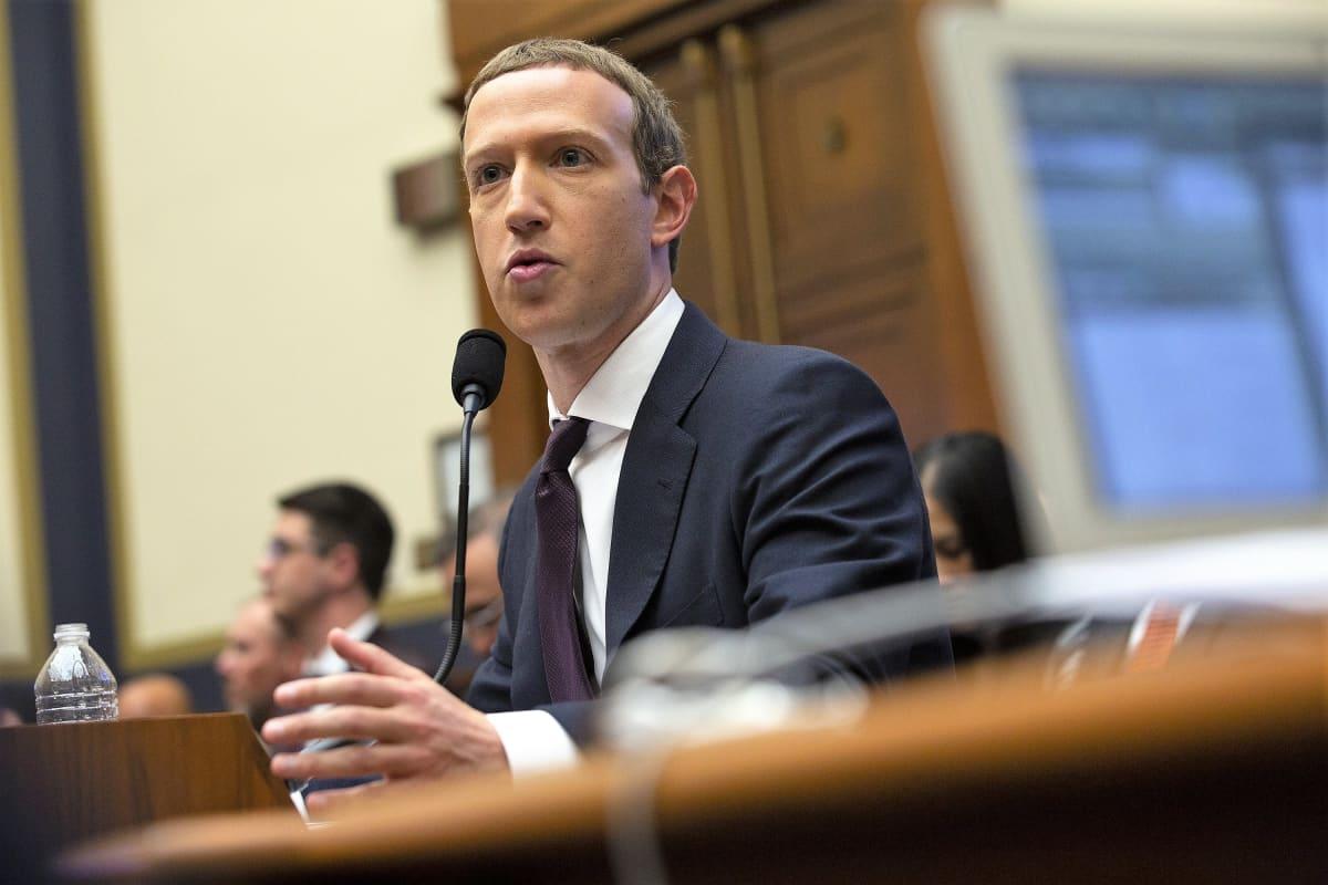 Mark Zuckerberg istuu pöydän takana ja puhuu mikrofoniin.