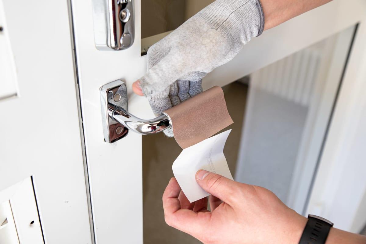 Covidsafe tarrapinnoitetta asennetaan ovenkahvaan.