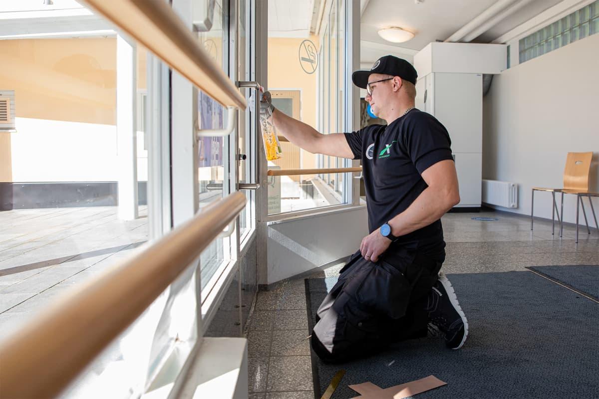 Henri Kaipio puhdistaa ovenkahvan ennen covidsafe tarrapinnoitteen asentamista.