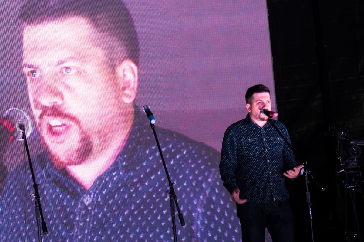 Leonid Volkov seisoo lavalla ja puhuu mikrofoniin. Taustalla näkyy suurelle kankaalle heijastettuna kuva hänestä puhumassa.