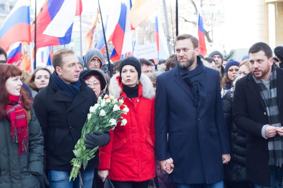 Venäjän oppositio marssilla. Kuvan oikeassa reunassa ovat Julija Navalnaja, Aleksi Navalnyi, Leonid Volkov. Julija Navalnajalla on punainen takki, Navalnyillä tummanharmaa päällystakki ja Volkovilla musta takki. Taustalla kannetaan Venäjän lippuja.