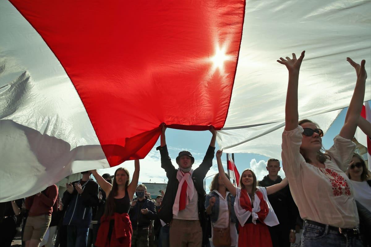 Mielenosoittajat kannattelevat punavalkoista Valko-Venäjän lippua. Aurinko loistaa lipun läpi.