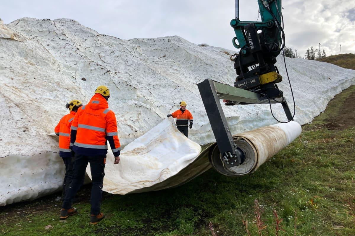 Levi Ski Resortin työntekijät purkavat viiroja säilölumikinosten päältä.