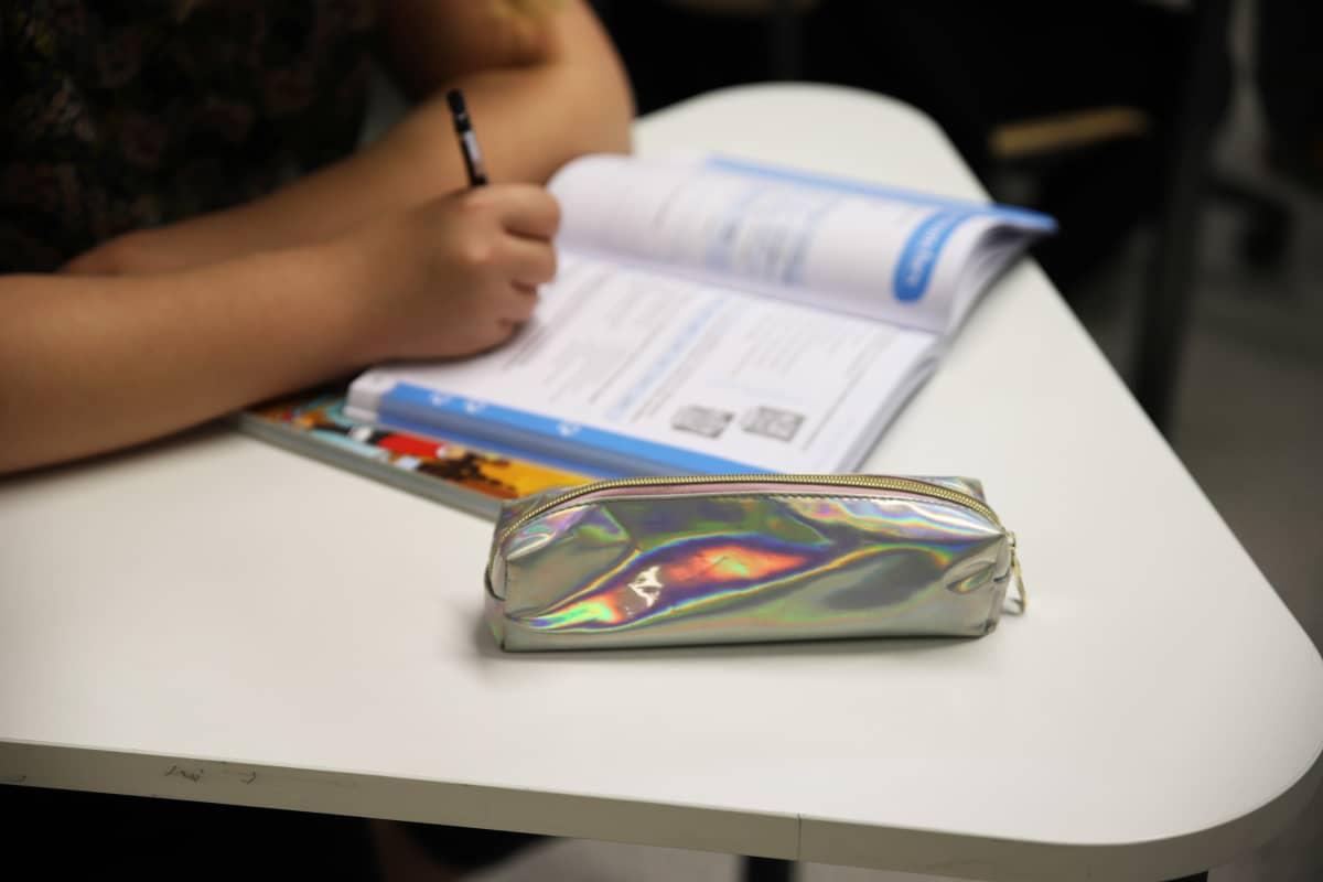 Oppilas kirjoittaa koulukirjaansa.