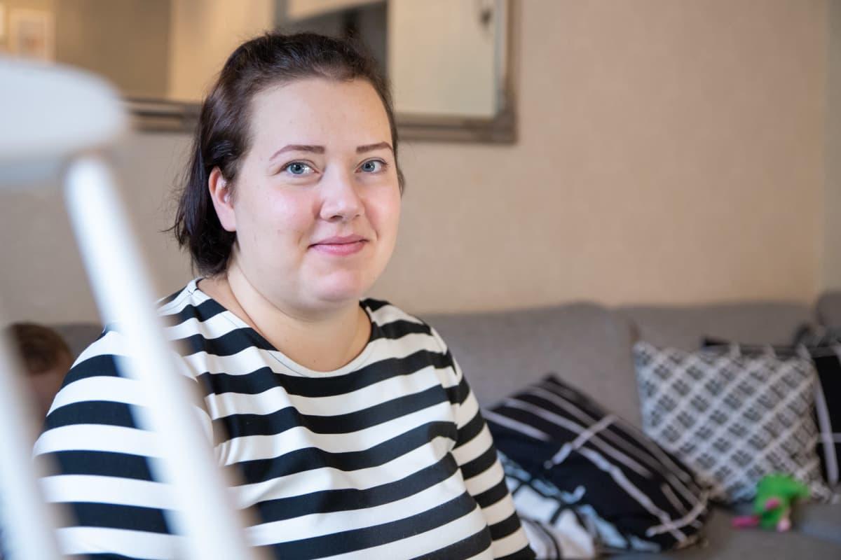 Sonja Kyrönlahti istuu olohuoneen sohvalla.