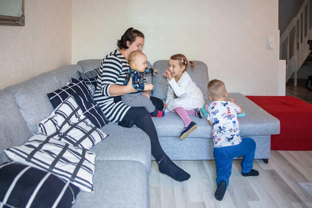 Sonja Kyrönlahti leikkii sohvalla lapsiensa Esterin, Eemelin ja Eetun kanssa.